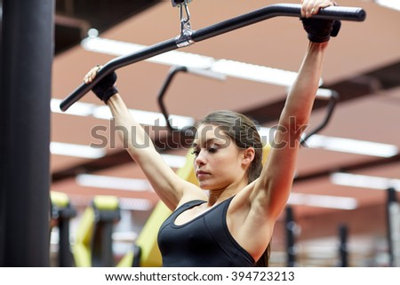 sport, fitness, bodybuilding, lifestyle and people concept - woman flexing arm muscles on cable machine in gym - stock photo