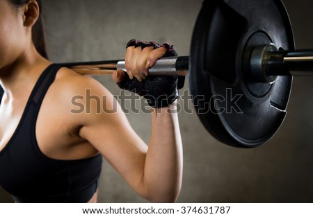 sport, fitness, bodybuilding, weightlifting and people concept - close up of young woman with barbell flexing muscles in gym - stock photo