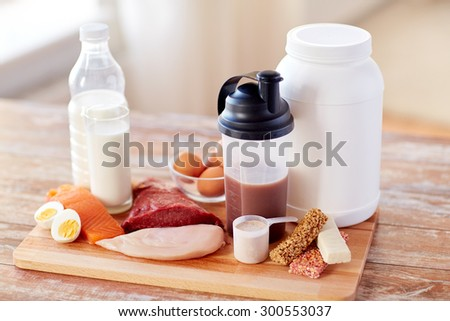 sport, fitness, healthy lifestyle, diet and people concept - close up of natural protein food and additive on wooden table - stock photo