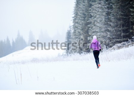 Sport, fitness inspiration and motivation. Young happy woman cross country running in mountains on snow, winter day. Female trail runner jogging exercising outdoors in white environemnt. - stock photo