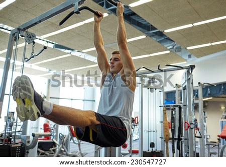 sport, fitness, lifestyle and people concept - young man flexing abdominal muscles on pull-up bar in gym - stock photo