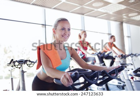 sport, fitness, lifestyle, equipment and people concept - group of women riding on exercise bike in gym - stock photo