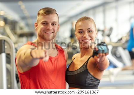 sport, fitness, lifestyle, gesture and people concept - happy man and woman pointing finger to you in gym - stock photo