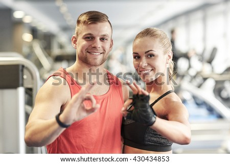 sport, fitness, lifestyle, gesture and people concept - smiling man and woman showing ok hand sign in gym - stock photo