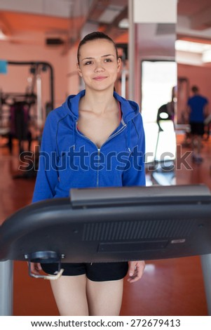 sport, fitness, lifestyle, technology and people concept - smiling woman exercising on treadmill in gym. - stock photo