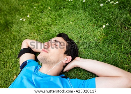 Sport fitness man relaxing listening to music after training outdoor in a city park . Young male athlete resting relaxing lying on grass after running and training exercise outside in summer. - stock photo