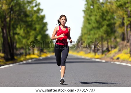Sport fitness running woman jogging during outdoor workout. Beautiful young female athlete runner training for marathon on forest road in spring or summer. Mixed race Asian woman fitness model. - stock photo