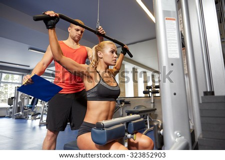 sport, fitness, teamwork and people concept - young woman flexing muscles on gym machine and personal trainer with clipboard - stock photo