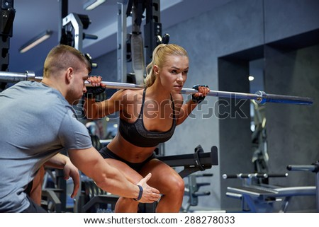 sport, fitness, teamwork, bodybuilding and people concept - young woman and personal trainer with bar flexing muscles in gym - stock photo