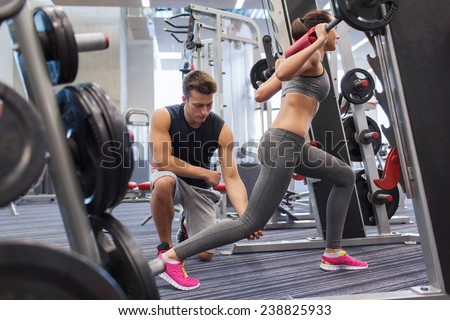 sport, fitness, teamwork, weightlifting and people concept - young man and personal trainer with barbell flexing muscles in gym - stock photo