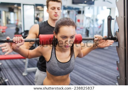 sport, fitness, teamwork, weightlifting and people concept - young woman and personal trainer with barbell flexing muscles in gym - stock photo