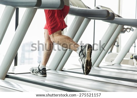 sport, fitness, technology and people concept - close up of male legs running on treadmill in gym - stock photo