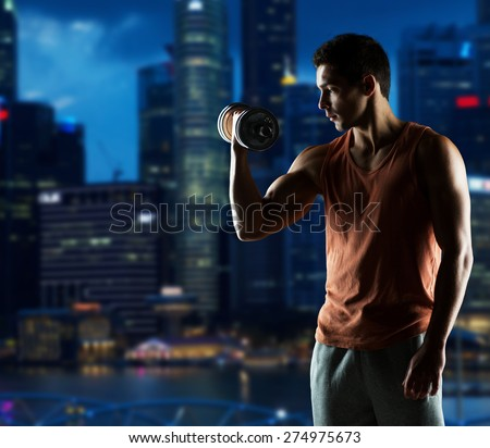 sport, fitness, weightlifting, bodybuilding and people concept - young man with dumbbell flexing biceps over night city background - stock photo