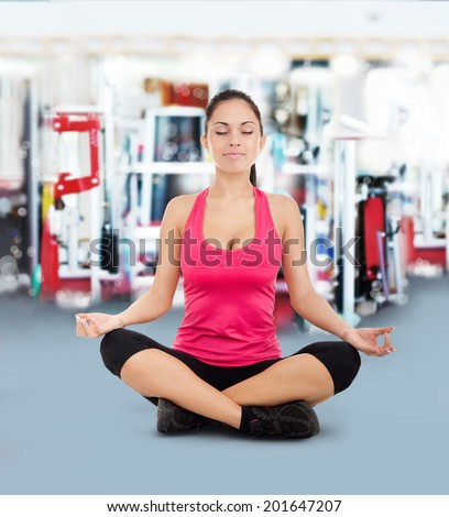 sport fitness woman doing yoga exercises in gym, young healthy girl sitting in lotus pose - stock photo