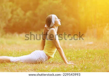Sport, fitness, yoga - concept, slim woman doing exercise outdoors on the grass - stock photo