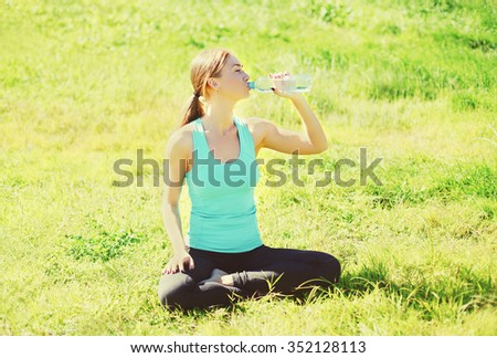 Sport, fitness, yoga concept - woman sitting on grass and drinking water from bottle in sunny summer day - stock photo