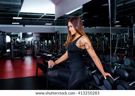 Sport, Fitness. Young woman at the gym.Girl doing exercise with dumbbells in the gym. Attractive fitness woman, trained female body, lifestyle portrait. - stock photo
