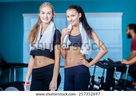 Sport friendship. Two friends are athletes in the gym and look at the camera while their friends involved in sports and pedaling on a stationary bike - stock photo