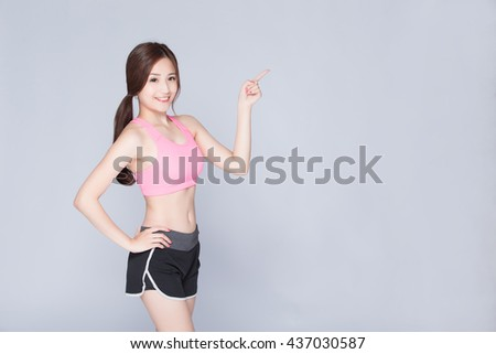 Sport girl pointing something isolated on gray background. Running fitness sport woman smiling happy. asian beauty - stock photo