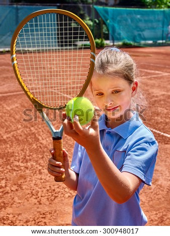 Sport kids girl with racket and ball on  brown tennis court. - stock photo