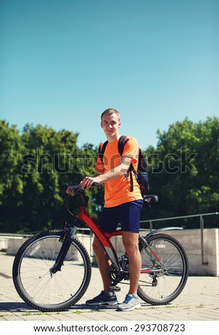 Sport, leisure and healthy lifestyle concept - young smiling man on a bicycle in summer day against the blue sky, male cyclist in profile - stock photo