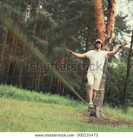 Sport, leisure, recreation and healthy active lifestyle concept - man slacklining walking and balancing on a rope, slackline in forest - stock photo