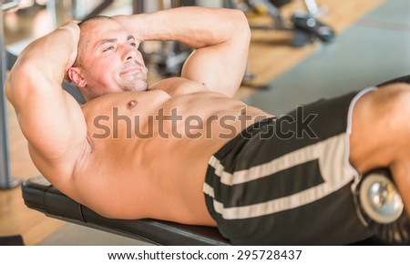 Sport, lifestyle and people concept - young man making abdominal exercises in gym. - stock photo