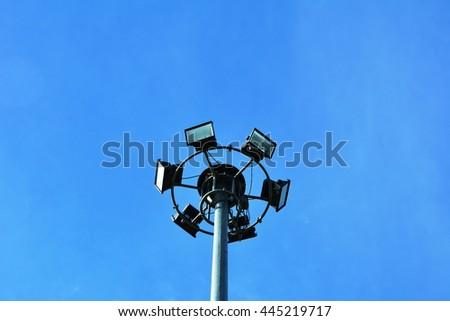 Sport light post on blue sky background - stock photo