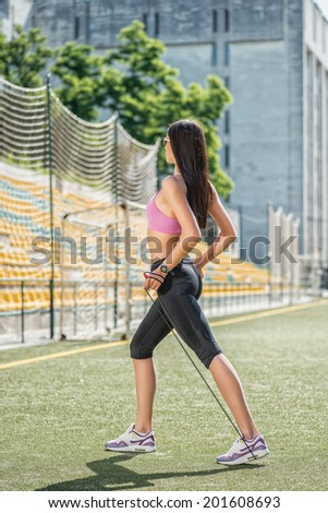 Sport load on feet. Young and charming woman in sunglasses and sportswear standing on the football field and skipping rope stretches back view - stock photo