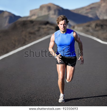 Sport man running. Runner sprinting training for marathon. Young strong male fitness model during run outdoors in beautiful landscape. - stock photo