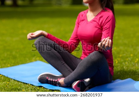 sport, meditation, yoga, fitness and people concept - close up of woman meditating on mat at park - stock photo