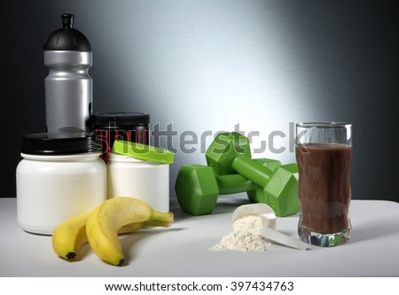 Sport Nutrition Supplement containers with glass of cocktail - stock photo