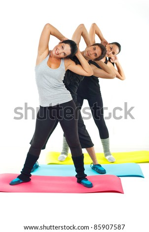 Sport people team standing on colorful mats and doing fitness exercises together - stock photo
