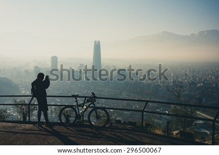 Sport photographer at the top of the hill. Santiago de Chile cityscape. - stock photo