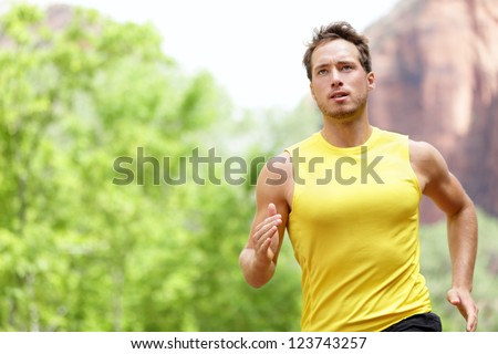 Sport - Runner. Man running with concentration, determination and strength towards goals and success in marathon. Fit male sport fitness model sprinting outdoors. - stock photo