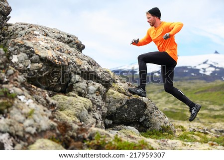 Sport running man in cross country trail run. Fit male runner exercise training and jumping outdoors in beautiful mountain nature landscape with Snaefellsjokull, Snaefellsnes, Iceland. - stock photo