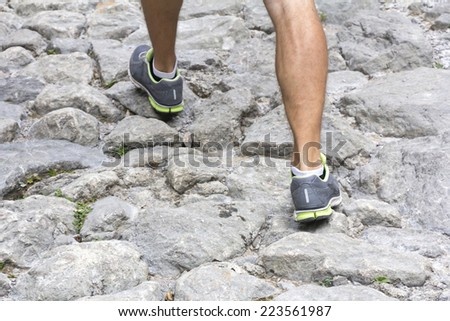 Sport shoes and exercise walking on the mountain trail - stock photo