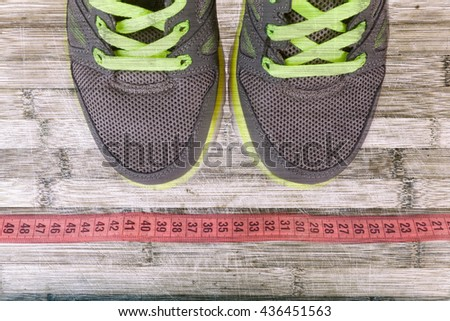 Sport shoes and pink measure tape on wooden background. - stock photo