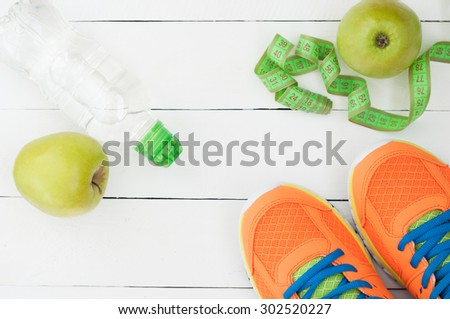 Sport shoes, apple and bottle of water on white wooden background. Sport accessories. Selective focus - stock photo