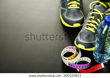 Sport shoes, measuring tape and water on grey background - stock photo