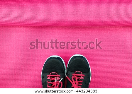 Sport shoes on pink yoga mat background, Fitness accessories and exercise Equipment, No gym workout concept. - stock photo