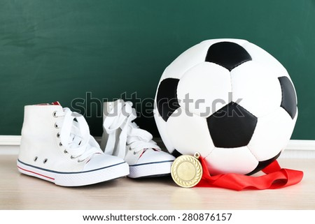 Sport shoes, soccer ball and golden medal on blackboard background - stock photo