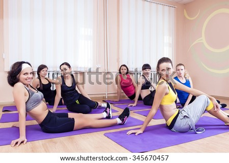 Sport, Training anf Healthy Lifestyle Concepts. Group of Seven Caucasian Women Resting on Floor Mats During Gym Fitness Class. Horizontal Image Orientation - stock photo