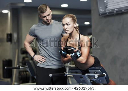 sport, training, fitness, lifestyle and people concept - young woman with personal trainer flexing back and abdominal muscles on bench in gym - stock photo
