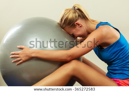 Sport, training, gym and lifestyle concept. Young attractive slim woman in sportswear doing fitness exercises with fit ball at home - stock photo
