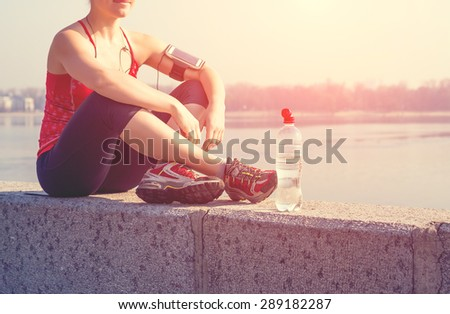 Sport woman having a rest during training outside in city quay in the morning - stock photo