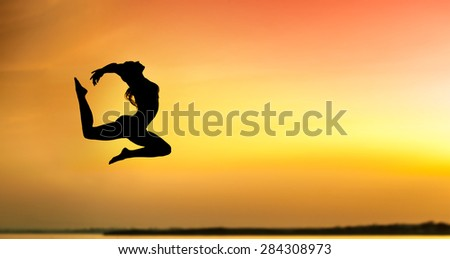 Sport woman jumping against beautiful sunrise. Freedom, enjoyment concept. - stock photo