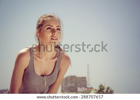 Sport woman listening to music while exercising with headphones in the park on the street - stock photo