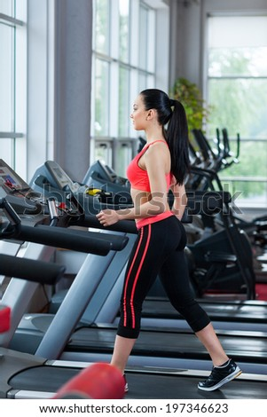 sport woman walk on cardio machine at the gym run exercising fitness center - stock photo