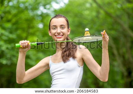 Sport woman with badminton racket and shuttlecock in the park - stock photo